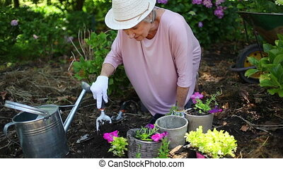 Retired woman planting flowers in a garden