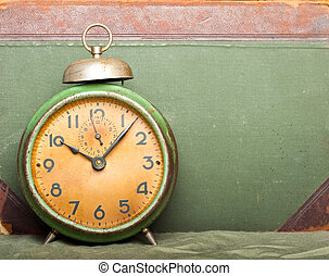 vintage clock with old book on background