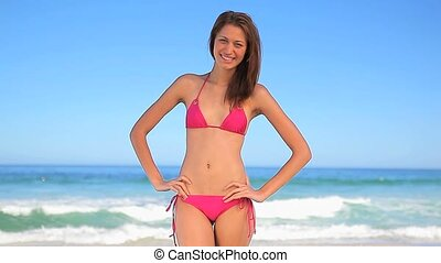 Happy brunette woman standing with her hands on her hips on...