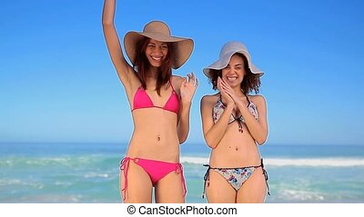 Happy women standing while wearing straw hats on the beach