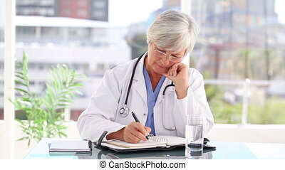 Thoughtful practitioner writing on a calendar in a bright...