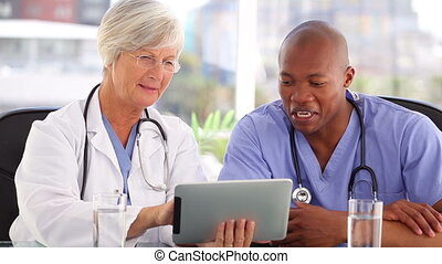 Happy doctors working with a touchscreen