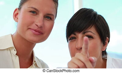 Two businesswomen working together in a bright office