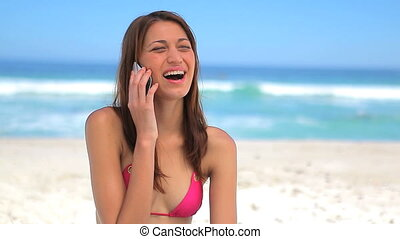 Happy brunette woman talking on the phone on the beach