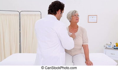 Serious mature woman being examined in a medical office