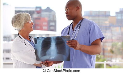 Two smiling doctors looking at an x-ray
