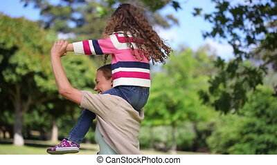Woman turning while carrying her daughter on the shoulders...