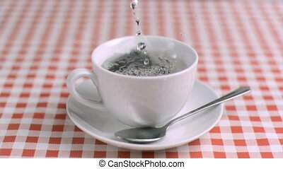 Water poured in super slow motion in a cup with tea on a...