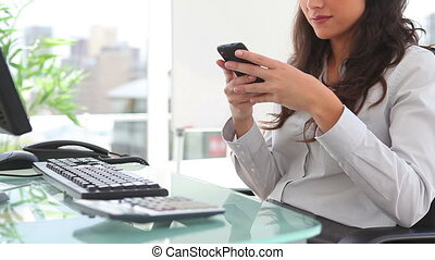 Businesswoman writing a text message in an office