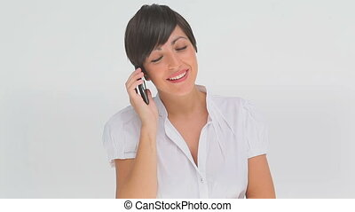 Businesswoman talking on a phone against a white background