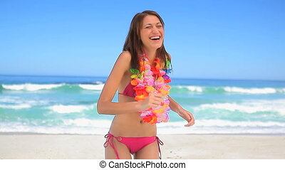 Brunette woman wearing a flower garland on the beach