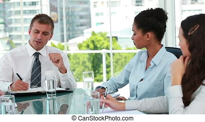Businessman talking with employees in a meeting in a bright...