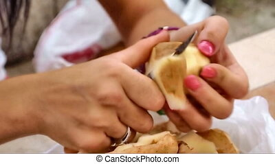 Peeling potatoes - Young woman peeling potatoes close up