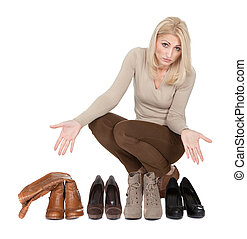 Beautiful young woman choosing shoes to wear. Isolated on...