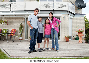 Caucasian family standing in front of house - Caucasian...
