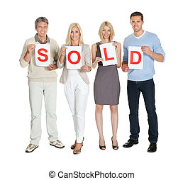 Group of people holding sold sign on white