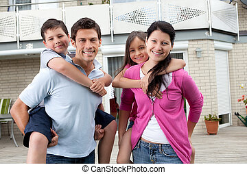 Happy family having fun outdoors at their home