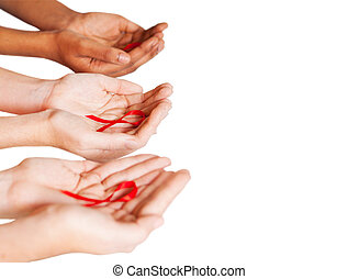 AIDS HIV awareness - hands holding red ribbon to rise AIDS...