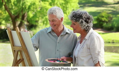 Smiling mature man painting in front of his wife in the...