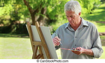 Smiling mature man drawing on a canvas in the countryside