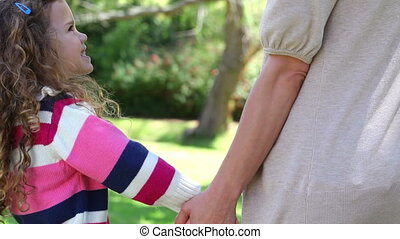 Daughter holding her mothers hand in a park