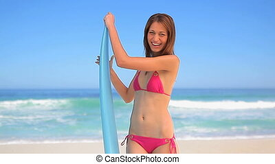 Smiling brunette holding a blue surfboard on the beach