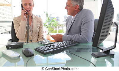 Businessman talking to his colleague as she makes a phone call