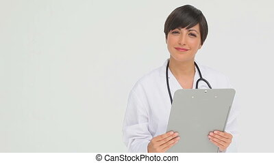 Doctor holding a clipboard against a grey background