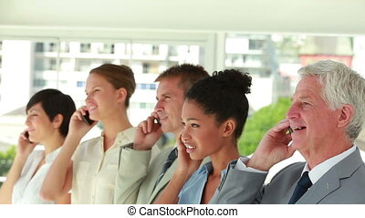 Business people of all ages smiling on the phone in a bright...