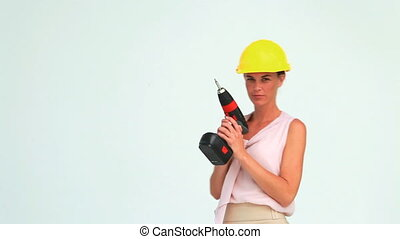 Woman with a safety helmet shooting with a screw gun in...