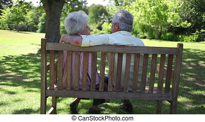 Rear view of a mature couple sitting on a bench in a park