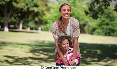 Woman embracing her daughter while standing in a park
