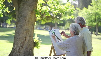 Mature couple painting trees in a park