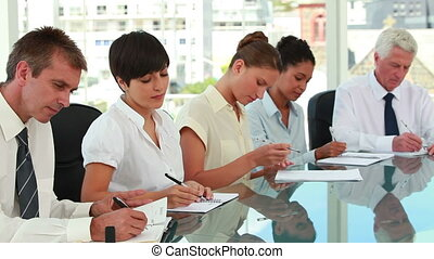 Business people taking notes while sitting at a meeting table