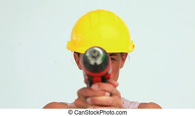 Businesswoman with safety helmet blowing on a screw gun