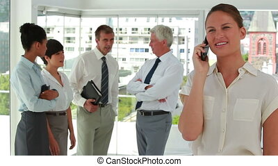 Businesswoman on the phone with colleagues in background