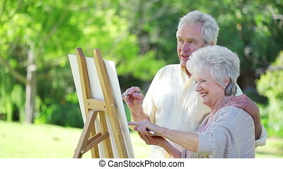 Retired woman showing something to her husband while...