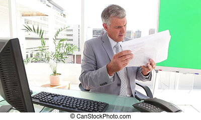 Businessman looking at sheets in an office