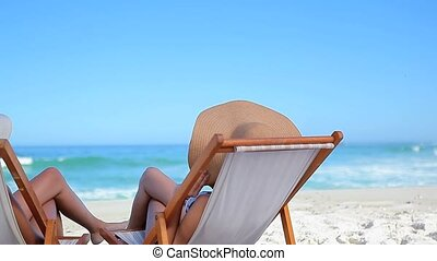 Peaceful women wearing hats while sitting on deck chairs on...