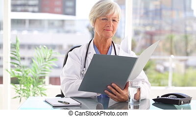 Smiling mature doctor looking at files in her bright office