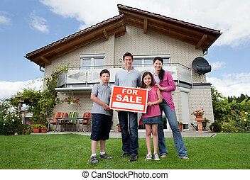 Family selling their home holding for sale sign - Portrait...