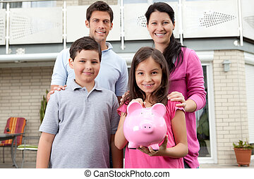 Little girl with her family holding a piggy bank