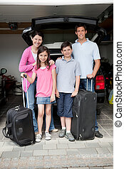 Happy family going on holiday standing by their car boot...