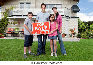 Happy family buying new house - Young happy family holding...