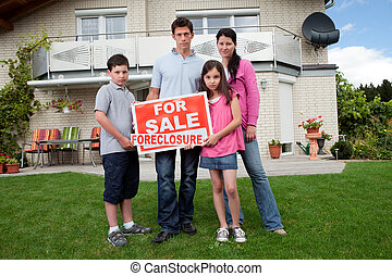Young family holding a foreclosure sign - Portrait of young...