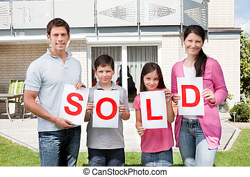 Family holding a sold sign outside their home - Portrait of...