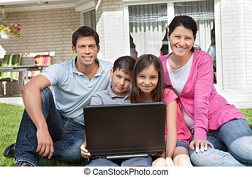 Happy family sitting together with laptop