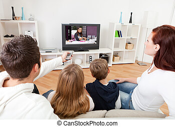 Young family watching TV at home - Young family watching TV...