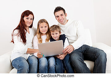 Happy family using laptop at home - Happy family spending...