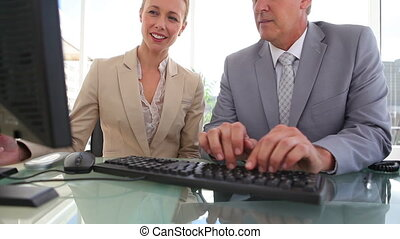 Businessman pointing at a screen with his colleague in an...